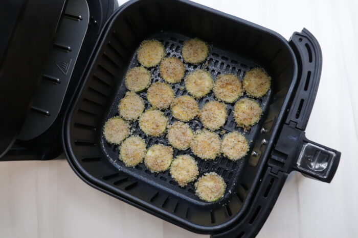 breaded zucchini chips in an air fryer before cooking