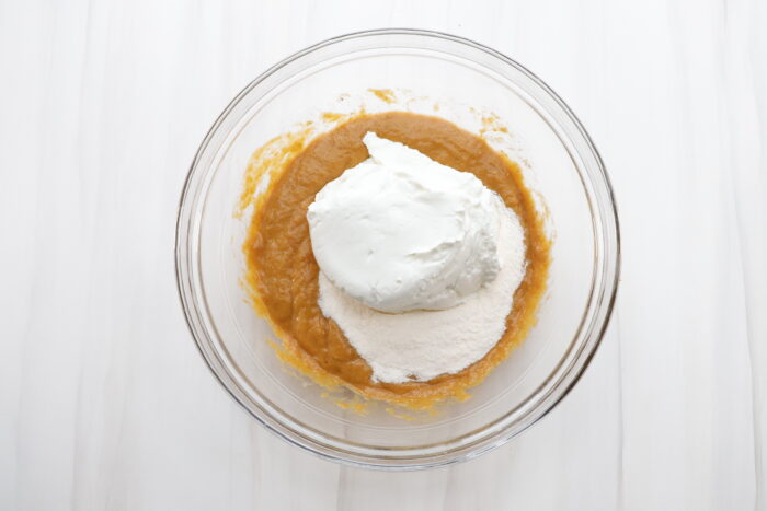 Greek yogurt added to pumpkin mixture in a glass bowl
